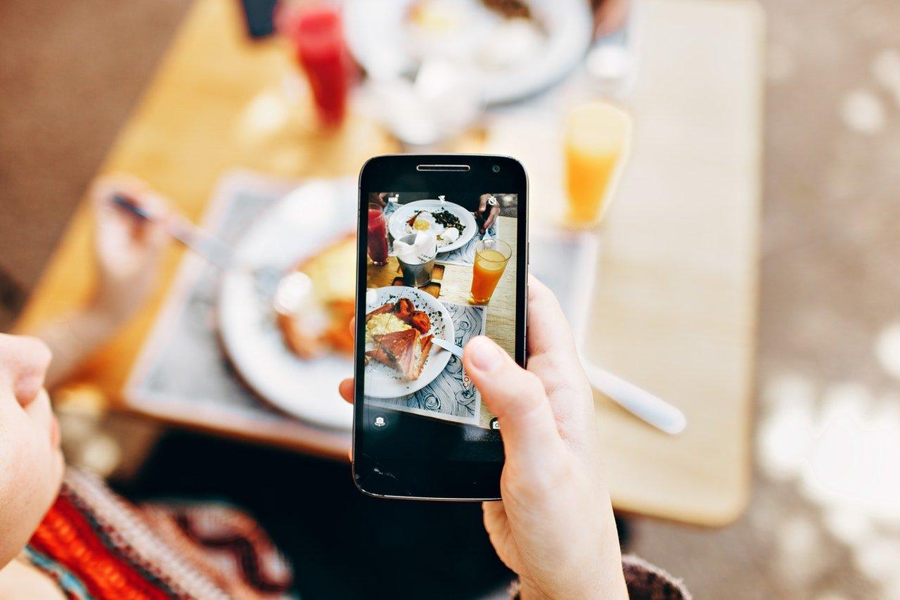 Woman taking picture of food Grubhub vs doordash