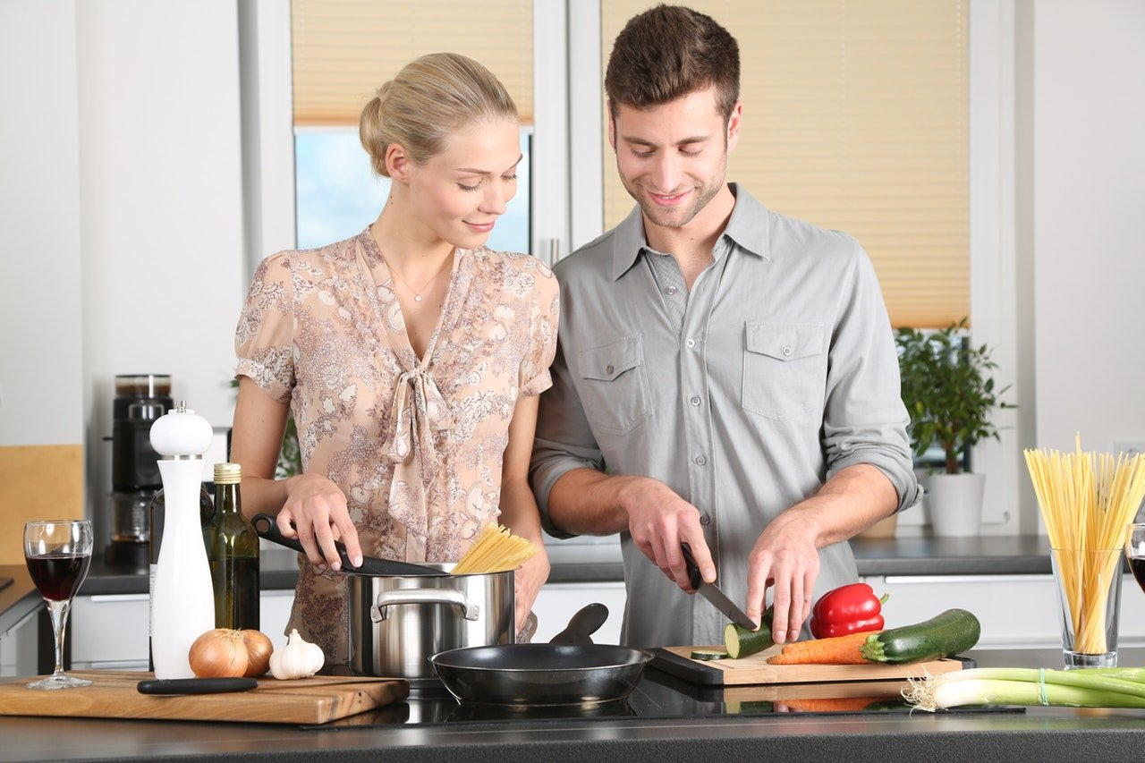 woman and man cooking in kitchen hello fresh vs blue apron